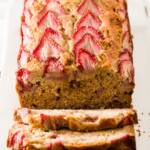 A loaf of strawberry banana bread with three slices falling down from it