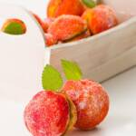 Two peach cookies in the foreground with a basket of cookies in the background